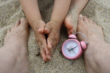 On the beach. Close up of mother and son, hands and feet