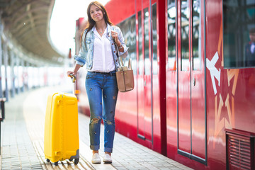 Young woman with luggage at a train station waiting for express