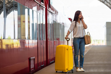 Young woman with luggage talking by cellphone at a train station