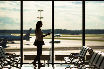 Silhouette of airline passenger in an airport lounge waiting for