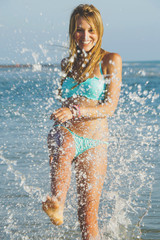 Young woman playing in the water at the beach
