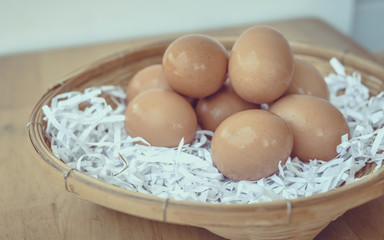 Eggs in a wicker basket on a wooden table