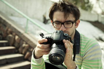 young man in spectacles with camera