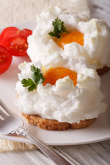 Beautiful food: fried eggs Orsini and tomatoes close-up. vertical