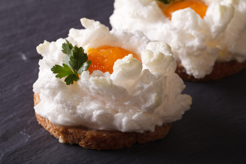 Eggs Orsini: baked whipped whites and yolk on toast. Horizontal closeup