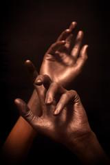beautiful man's hands in bronze paint