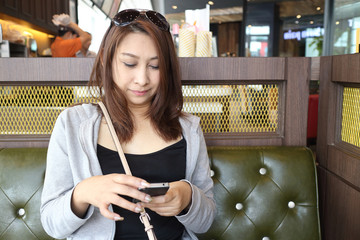 Cafe city lifestyle woman on phone drinking coffee texting text message on smartphone app sitting indoor in trendy urban cafe. Cool young modern mixed race Asian Caucasian female model in her 40s.