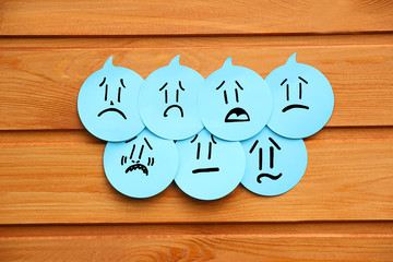 Sad emotions on blue stickers on wooden background. Group of negative emotions