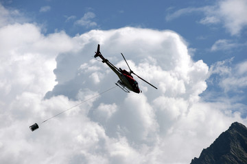 helicopter carries cargo in the Alps