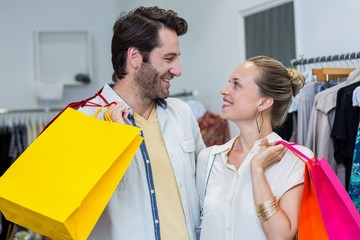 Smiling couple with shopping bags looking at each other