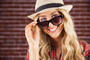Gorgeous smiling blonde hipster posing with sunglasses