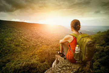 hiker sits on the edge of the cliff and enjoying sunrise Wall mural