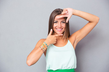Beautiful girl making frame gesture with fingers