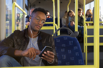 Young man using a smartphone on the bus