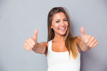 Cheerful lovely girl showing thumbs up