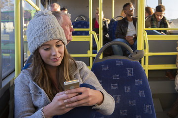 Woman using her phone on the bus