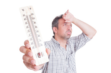 Sumer heat and heatwave concept with man holding thermometer