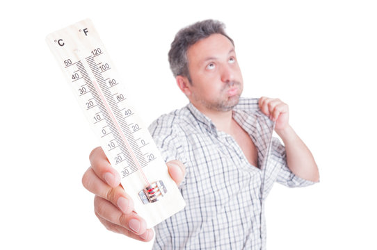 Sweaty man holding thermometer as summer heat concept