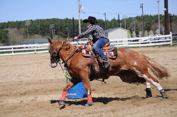 Young blonde woman barrel racing; A young woman turns around a barrel and begins racing to the finish line