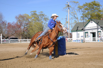 Young blonde woman barrel racing ; A young woman turns around a barrel and begins racing to the finish line