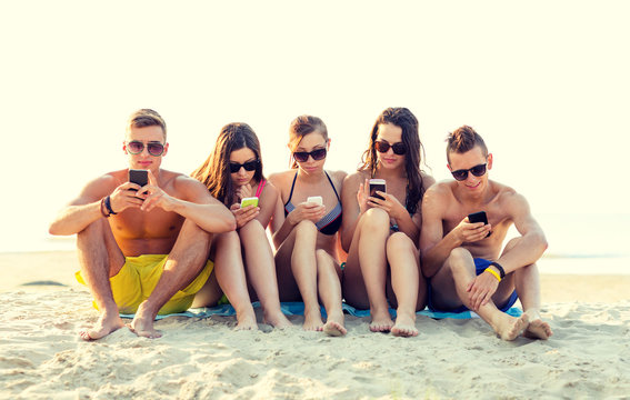 friends with smartphones on beach