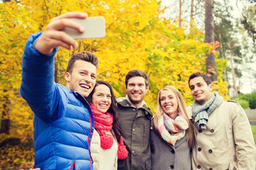 smiling friends with smartphone in city park