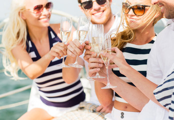 happy friends with glasses of champagne on yacht