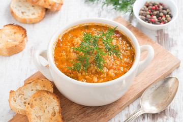 tomato soup with rice and vegetables in a white saucepan
