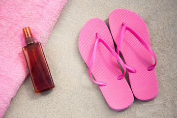 pink flip flops and suntan lotion bottle on sandy beach