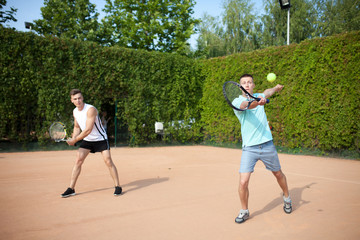 Mixed doubles player hitting tennis ball with partner