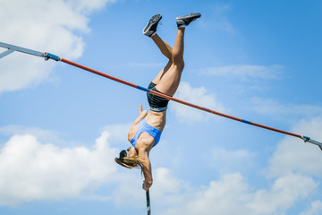 Girl athletes pole vault seems to reach the sky