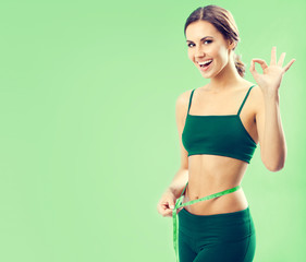 young woman in fitness wear with tape, on green