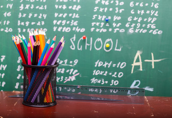 Colorful pencils of red yellow orange violet purple pink green and blue in stationary cup and ruler standing on brown school desk on written with white chalk blackboard backgroung on lesson of math