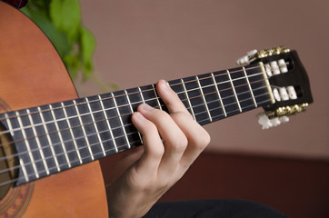 Closeup of chord on classic guitar. Selective focus on main finger