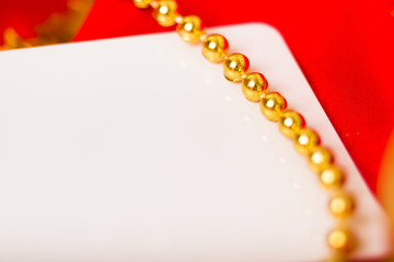 Gold beads and white card on red cloth. macro