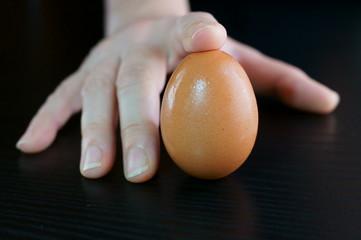 Uovo lesso sotto il dito della mano