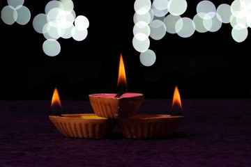 Three colorful diya with colored liquid like pink , yellow and orange are placed on to each other like a triangle shape and photographed against elegant dark background with beautiful bokeh.