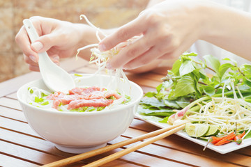 Young woman sprinkles sprouts to the Pho Bo in cafe, Vietnam