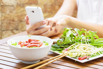 Young woman eating the Pho Bo and using a smartphone in Vietnam