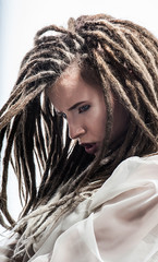 Beautiful girl with dreadlocks poses in white suit