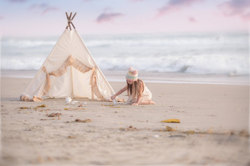 Girl sitting by a wigwam on the beach digging sand