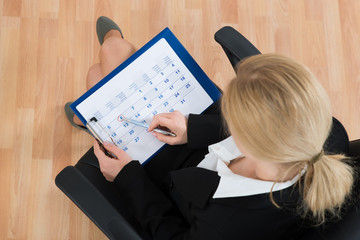Fototapete - Businesswoman Marking Date On Calendar
