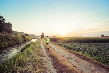 Wall Mural - Ragazzo che corre all'alba su strada di campagna in estate