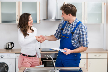 Woman Shaking Hands To Plumber