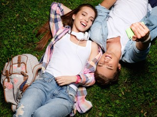 Cheerful young couple taking selfie lying on a grass in a park