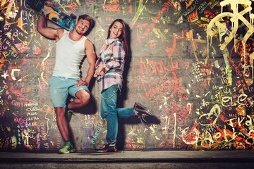 Young couple with skateboard  outdoors over graffiti painted wall