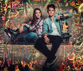 Young couple with skateboard outdoors against graffiti painted wall