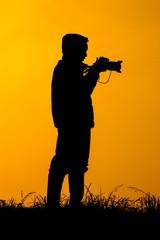 .Silhouette photographers take camera landscape