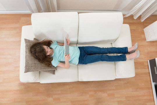 Girl On Sofa Using Digital Tablet