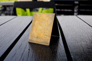 Blank old brown leather table card on wood table.
